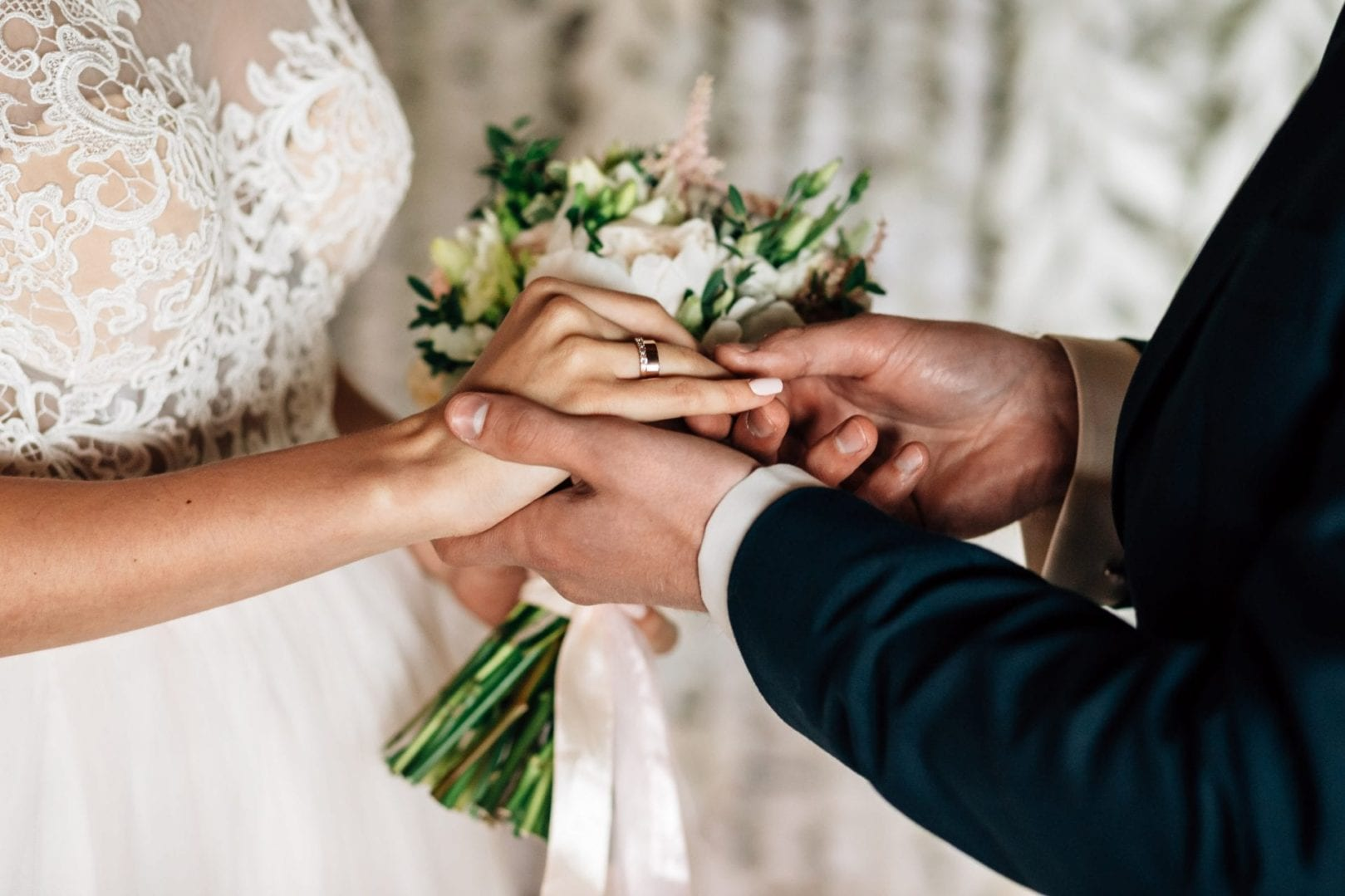 wedding ceremony close up of hand of man and woman exchanging wedding rings